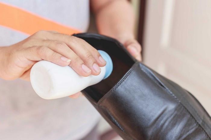Немного порошка рассыпают внутри обуви